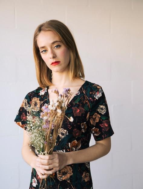 Mulher triste sensual com buquê de plantas secas Foto gratuita