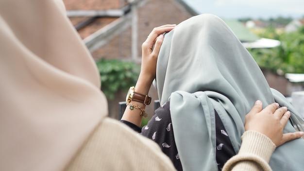 Mulher triste sentada na sala. amigos não desistem. menina triste e amigos apoiantes para resolver um problema. asiáticos Foto Premium