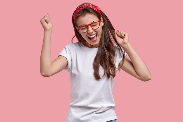 Mulher triunfante e alegre aperta os punhos, alegra-se com notícias positivas, exclama com alegria, modela o espaço rosa Foto gratuita
