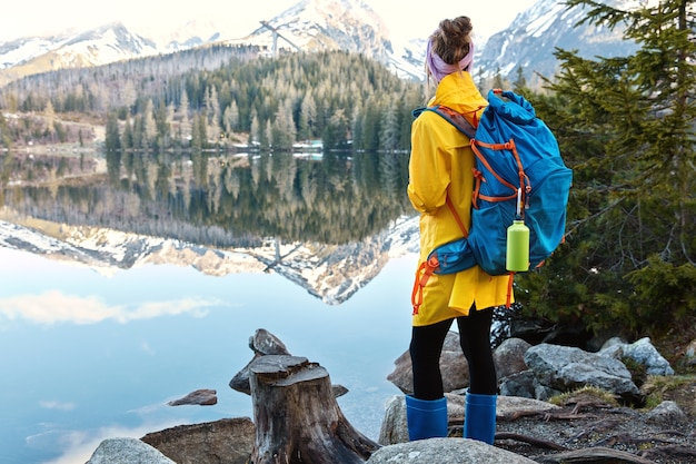 Mulher turista fica na margem de um belo lago de montanha, aprecia paisagens majestosas e natureza Foto gratuita