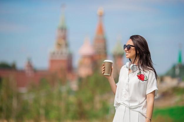 Mulher urbana jovem feliz bebendo café na cidade europeia. Foto Premium