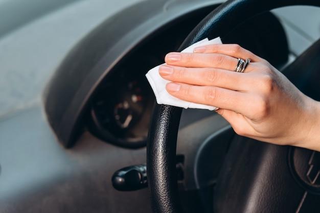 Mulher usa um desinfetante enquanto dirige um carro. precauções durante a epidemia de coronavírus. fusível de covid-19. garota com uma máscara médica em um carro. Foto Premium
