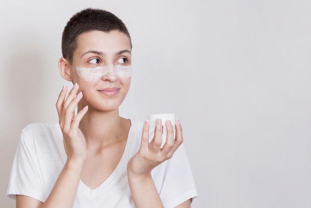 Mulher usando creme para a pele no rosto Foto gratuita