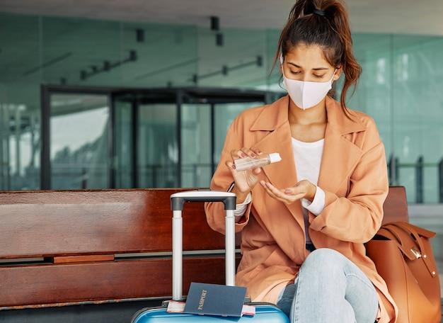Mulher usando desinfetante para as mãos no aeroporto durante a pandemia Foto Premium