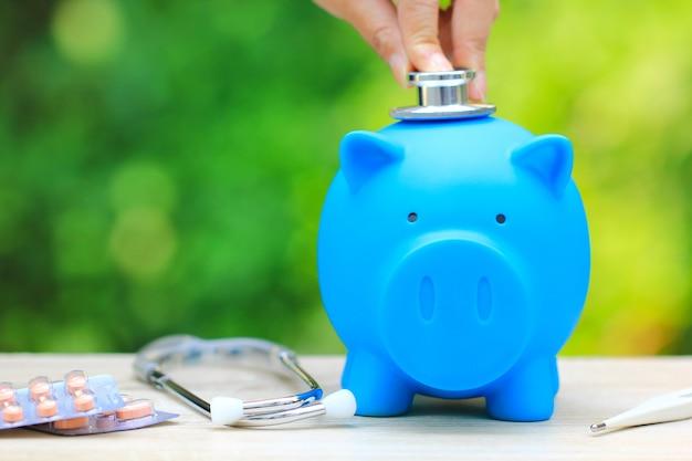 Mulher, usando, estetoscópio, cheque, azul, piggy, termômetro, medicina Foto Premium