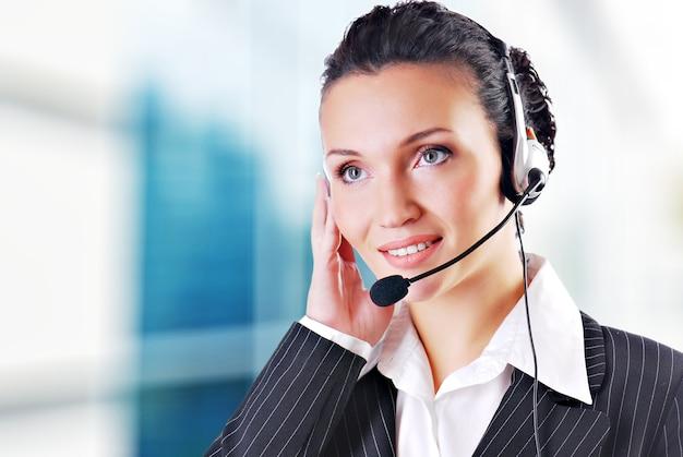 Mulher usando fone de ouvido no escritório; poderia ser recepcionista Foto gratuita