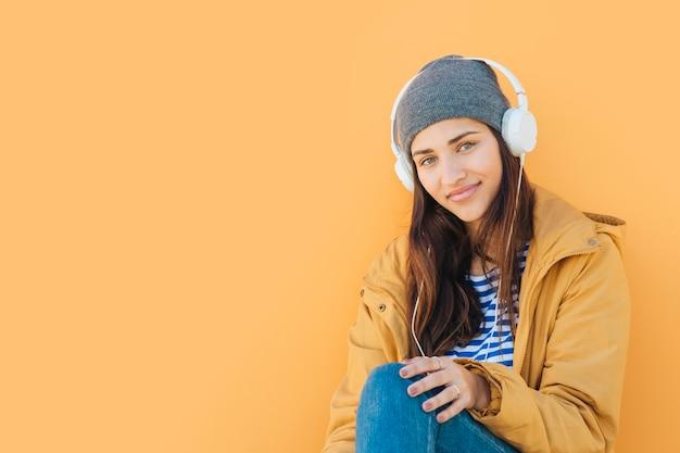 Mulher usando fone de ouvido olhando para a câmera, sentado na frente do pano de fundo amarelo liso Foto gratuita