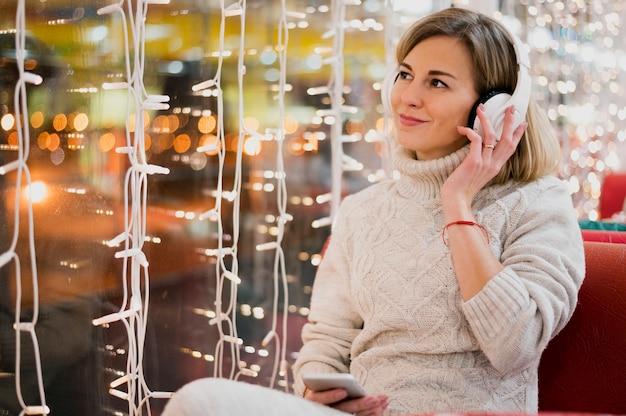 Mulher usando fones de ouvido perto de luzes de natal Foto gratuita