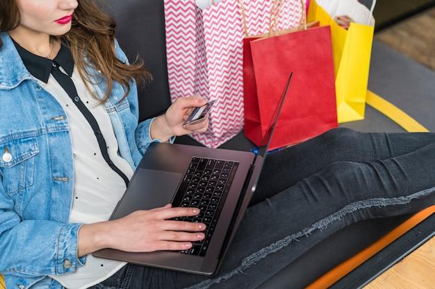 Mulher usando laptop e cartão de crédito para compras on-line Foto gratuita