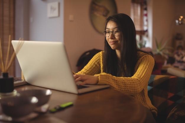 Mulher usando laptop na mesa da sala Foto gratuita