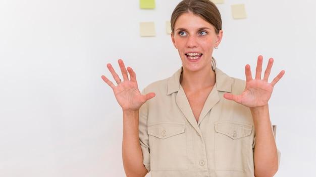 Mulher usando linguagem de sinais para transmitir algo Foto gratuita