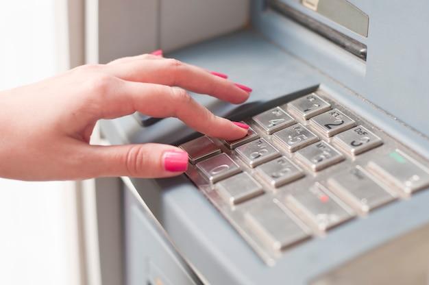 Mulher usando máquina bancária. fechar-se Foto gratuita