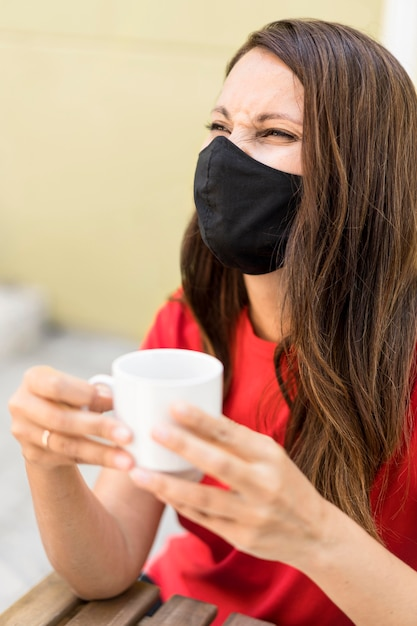 Mulher usando máscara de tecido e segurando uma xícara de café Foto gratuita