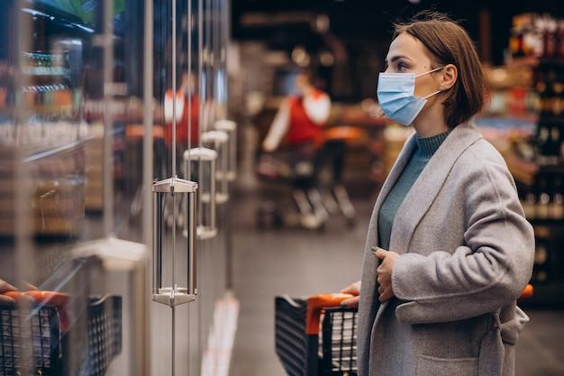Mulher usando máscara e fazendo compras em um supermercado Foto gratuita