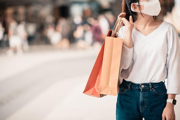 Mulher usando máscara protetora, segurando sacos de papel. Foto Premium