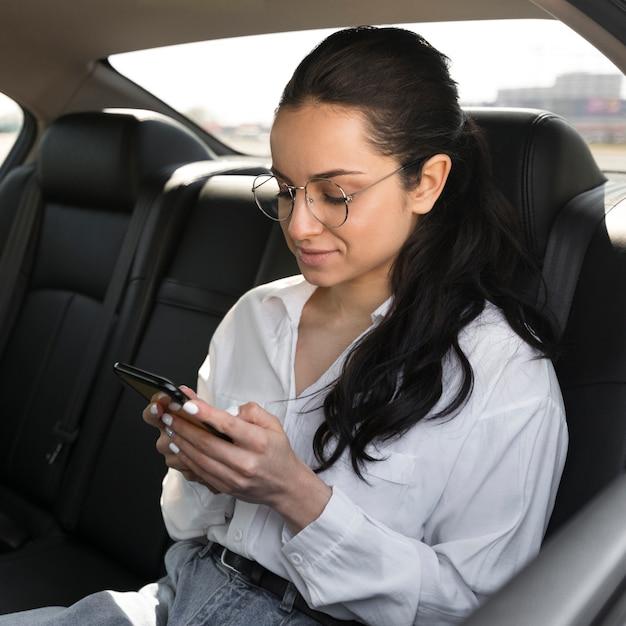 Mulher usando óculos de leitura no carro Foto gratuita