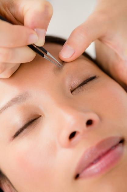 Mulher usando pinças na sobrancelha do paciente Foto Premium