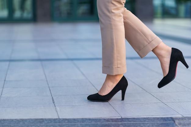 Mulher usando sapatos de salto alto pretos clássicos. modelo posando na rua. roupa elegante. fechar-se. Foto gratuita