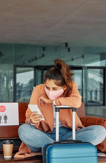 Mulher usando seu smartphone no aeroporto enquanto se apoiava em sua bagagem durante a pandemia Foto Premium