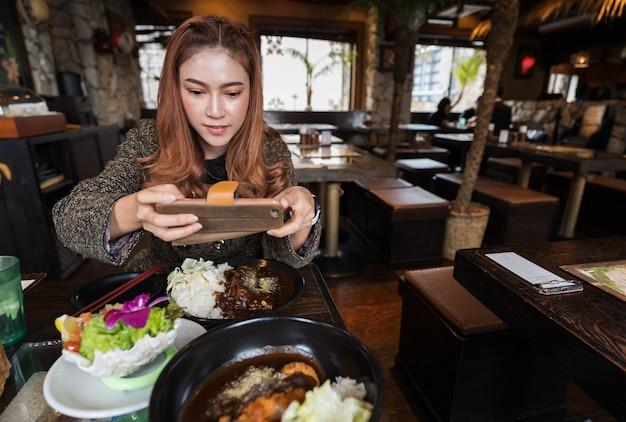 Mulher, usando, smartphone, levando uma foto, de, alimento, em, restaurante Foto Premium