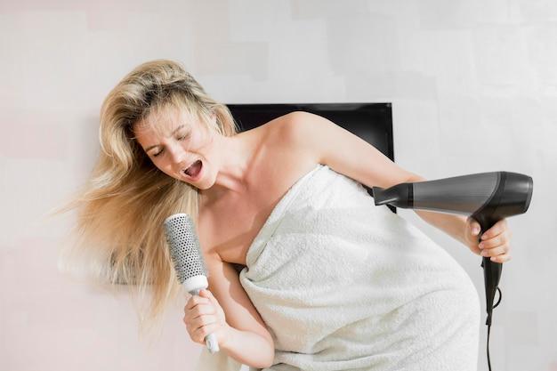 Mulher usando sua escova de cabelo como microfone Foto gratuita