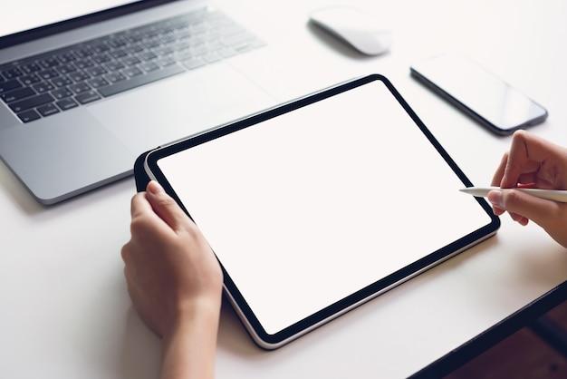 Mulher, usando, tabuleta, tela, em branco, e, laptop, ligado, a, tabela, mock, cima, para, promover, seu, produtos Foto Premium