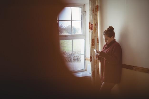 Mulher usando telefone celular perto da janela em casa Foto gratuita