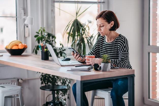 Mulher usando telefone inteligente e bebendo café Foto Premium