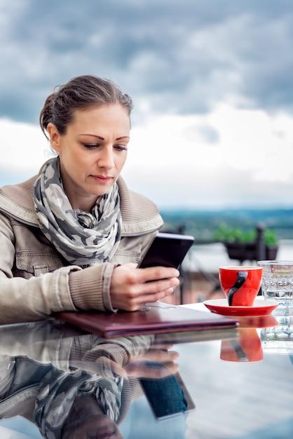 Mulher usando telefone inteligente no café Foto Premium
