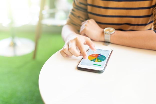 Mulher usando telefone inteligente para verificar dados no café Foto Premium