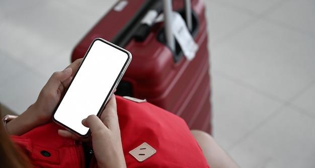Mulher, usando, telefone móvel, com, um, vermelho, bagagem, para, viajando, em, terminal, aeroporto Foto Premium