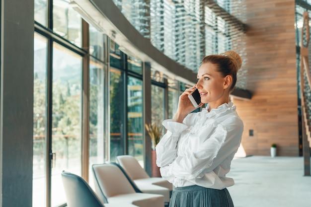 Mulher, usando, telefone móvel, em, escritório Foto Premium