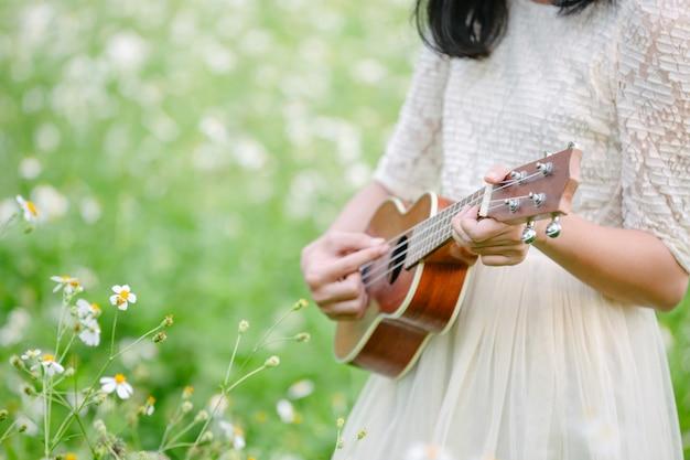 Mulher usando um vestido branco bonito e tocando ukulele Foto gratuita