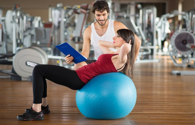Mulher usando uma bola de fitness para malhar com um personal trainer Foto Premium