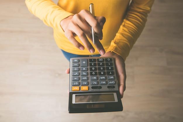 Mulher usando uma calculadora com uma caneta na mão Foto Premium
