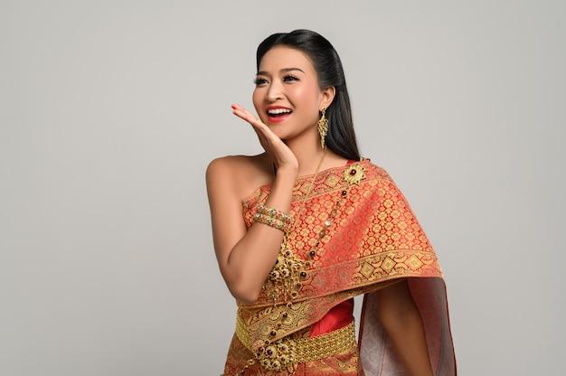 Mulher usando vestido tailandês que fez um símbolo de mão Foto gratuita
