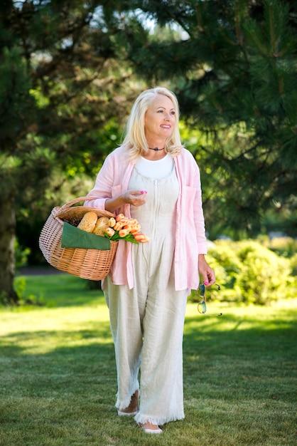 Mulher velha com uma cesta andando no prado Foto gratuita