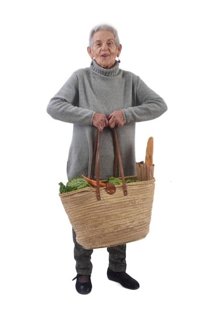 Mulher velha com uma cesta pesando muito Foto Premium
