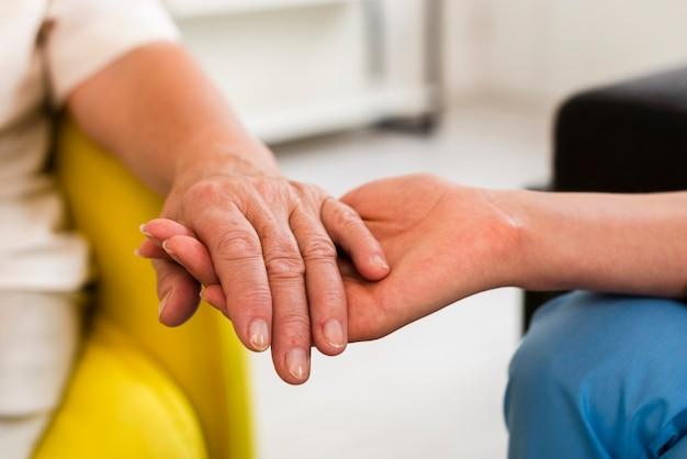 Mulher velha e enfermeira de mãos dadas close-up Foto gratuita