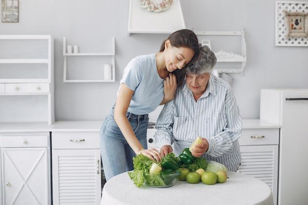 Mulher velha em uma cozinha com jovem neta Foto gratuita
