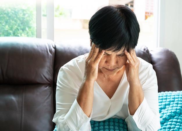 Mulher velha que sofre de dor de cabeça, estresse, enxaqueca, conceito de problema de saúde Foto Premium
