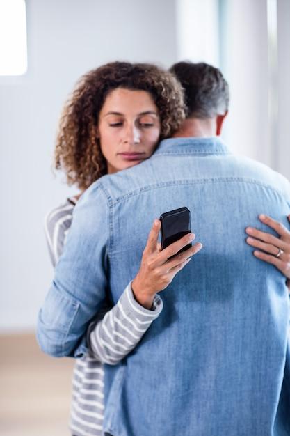Mulher verificando seu telefone celular enquanto abraçava um homem Foto Premium