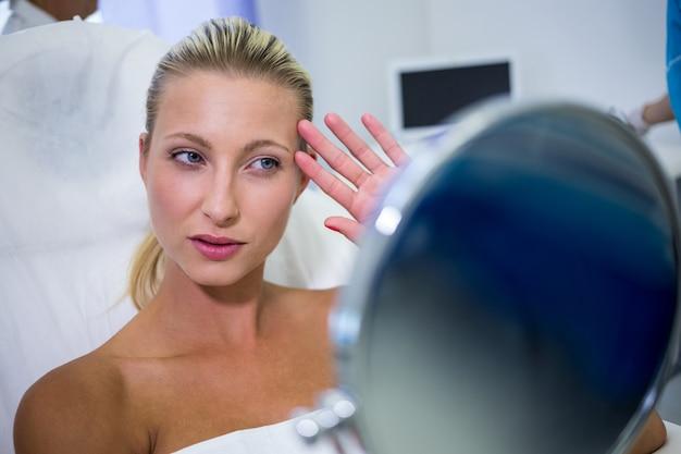 Mulher verificando sua pele no espelho depois de receber tratamento cosmético Foto gratuita