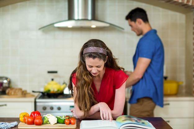 Mulher, verificar, a, receita, livro, em, cozinha, enquanto, homem, cozinhar, ligado, fogão, em, fundo Foto Premium