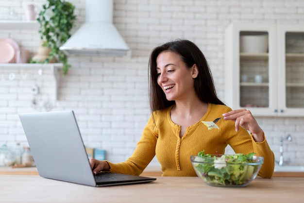 Mulher, verificar, laptop, e, comer, salada Foto gratuita