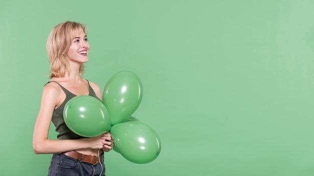 Mulher vestida casual, segurando balões Foto gratuita