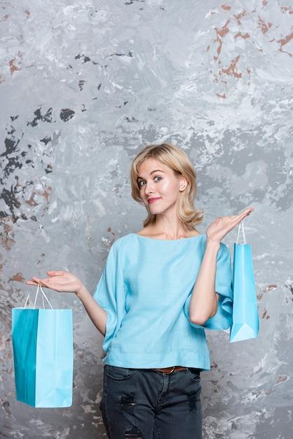 Mulher vestida casual, segurando sacos de papel Foto gratuita