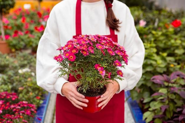 Mulher vestida com roupas de jardinagem, segurando o vaso de flores Foto gratuita
