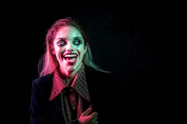 Mulher vestida como coringa rindo histericamente Foto gratuita