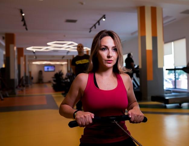 Mulher vestida de fitness rosa fazendo treinamento para os ombros em uma academia. Foto gratuita